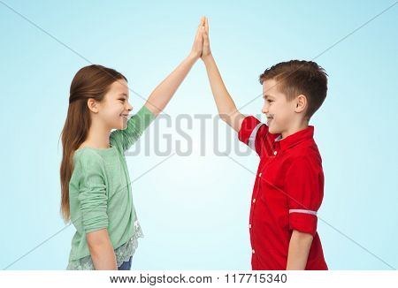 childhood, fashion, gesture and people concept - happy smiling boy and girl making high five over blue background