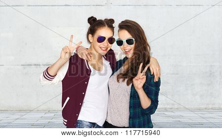 people, friendship, fashion, summer and teens concept - happy smiling pretty teenage girls in sunglasses showing peace hand sign over urban street background