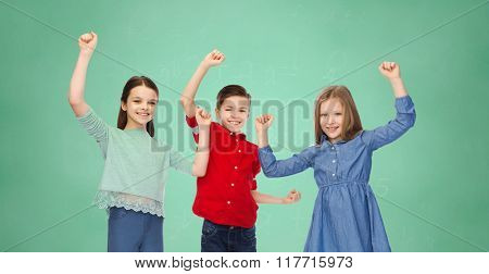 childhood, education, success, gesture and people concept - happy smiling boy and girls raising fists and celebrating victory over green school chalk board background