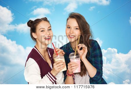 people, friends, teens and friendship concept - happy smiling pretty teenage girls drinking milk shakes and with straw over blue sky and clouds background
