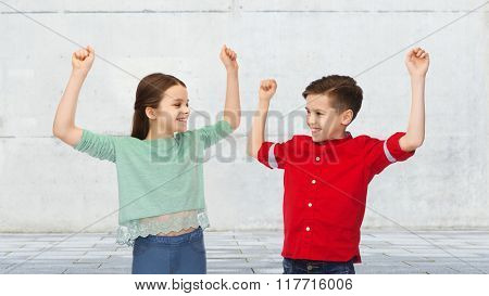 childhood, friendship, joy, gesture and people concept - happy smiling boy and girl raising fists and celebrating victory over urban street background