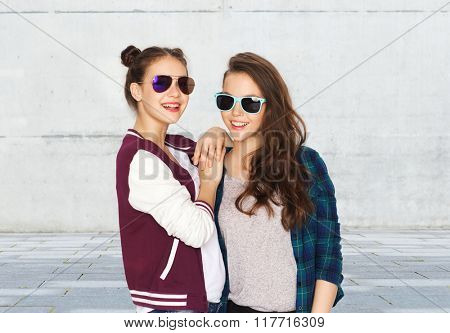 people, friendship, fashion, summer and teens concept - happy smiling pretty teenage girls in sunglasses over urban street background
