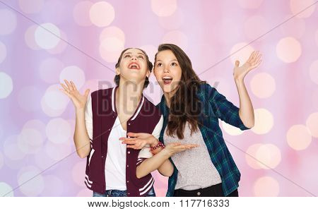 people, friends, teens and friendship concept - happy smiling pretty teenage girls hugging over pink holidays lights background