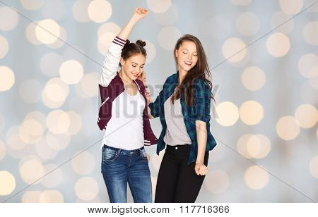 people, fun, teens and friendship concept - happy smiling pretty teenage girls dancing over holidays lights background