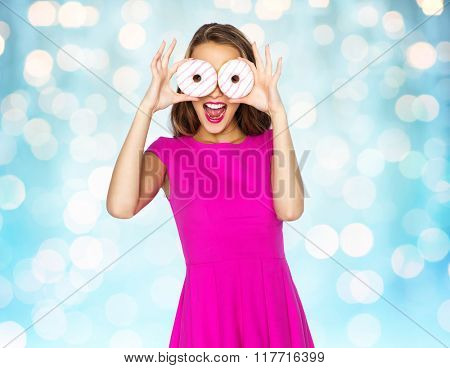 people, holidays, junk food and fast food concept - happy young woman or teen girl in pink dress having fun and looking through donuts over blue holidays lights background