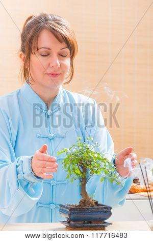 Beautiful woman wearing traditional chinese uniform meditating or healing with bonsai tree