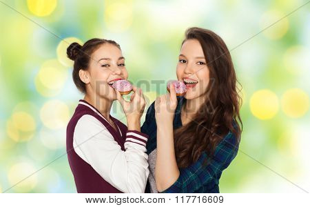people, friends, teens and friendship concept - happy smiling pretty teenage girls with donuts eating and having fun over green holidays lights background
