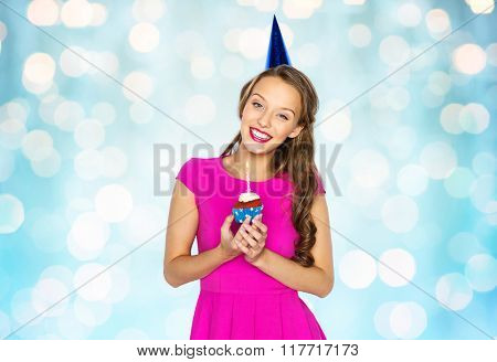 people, holidays and celebration concept - happy young woman or teen girl in pink dress and party cap holding birthday cupcake with burning candle over blue holidays lights background