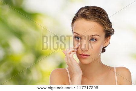 beauty, people, cosmetics, skincare and health concept - young woman applying cream to her face over green natural background