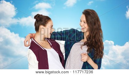 people, friends, teens and friendship concept - happy smiling pretty teenage girls hugging over blue sky and clouds background