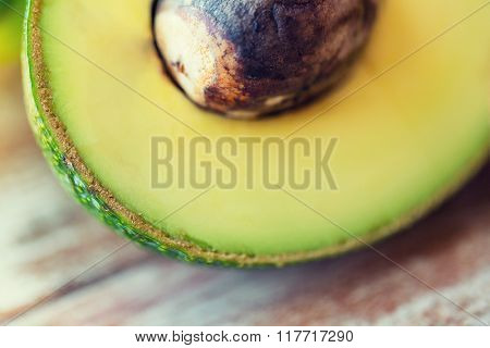 diet, vegetable food and objects concept - close up of ripe avocado cut with bone on table