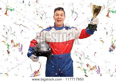 Joyful car racer holding a gold trophy and celebrating with confetti streamers around him isolated on white background