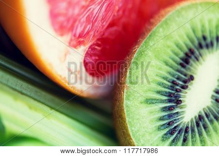 diet, food, healthy eating and objects concept - close up of ripe kiwi and grapefruit slices