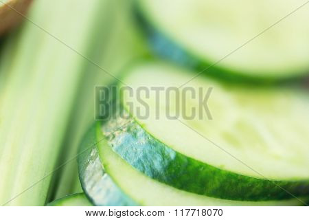 diet, vegetable food and objects concept - close up of cucumber slices and celery