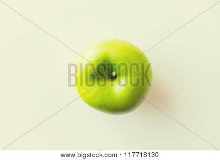 fruits, diet, eco food and objects concept - ripe green apple over white
