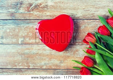 flowers, advertisement, valentines day and holidays concept - close up of red tulips and blank heart shaped chocolate box on wooden table