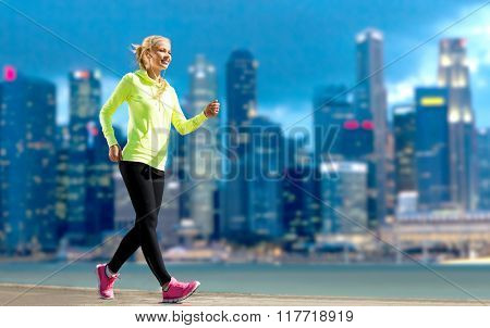 fitness, sport, people and healthy lifestyle concept - happy woman jogging over city street background