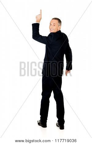 Full length businessman pointing upwards
