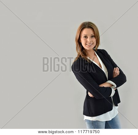 Stylish woman with arms crossed on grey background