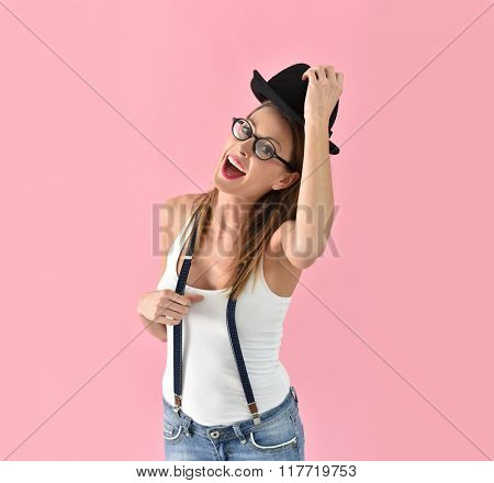Fashion girl with hat and eyeglasses, isolated on pink background