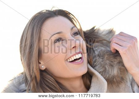 Portrait of cheerful girl with winter coat and fur hood
