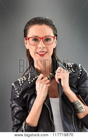 Beautiful trendy woman with red eyeglasses, grey background