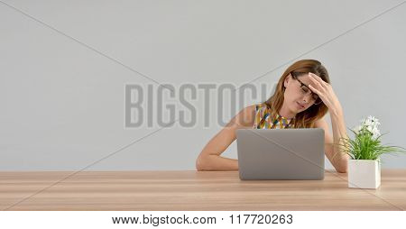 Woman in front of laptop having a headache, isolated
