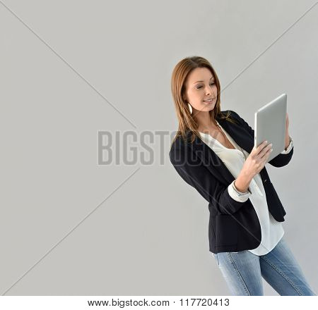 Beautiful woman using tablet, grey background