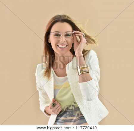 Trendy girl with eyeglasses, beige background