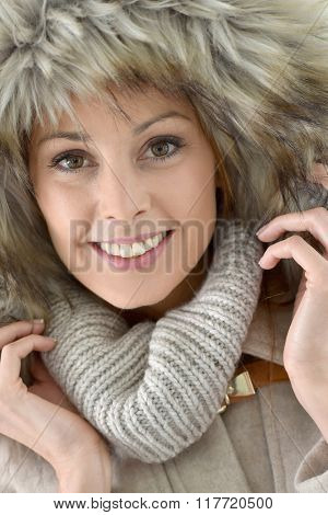 Closeup of woman wearing jacket with fur hood, isolated