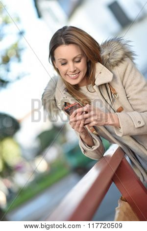 Trendy girl in city street sending text message with smartphone