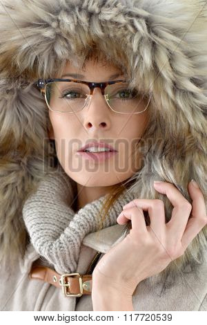 Closeup of woman wearing fur hood, isolated