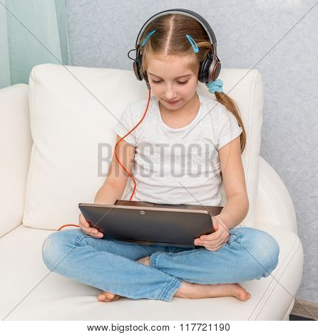 smiling little girl listening something with headphones and note book on sofa