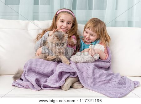 two lovely little girls with the cat covered with blanket embracing on sofa