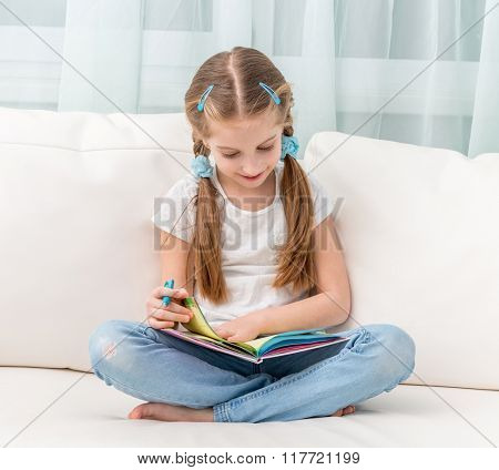 cute little girl filling in a friends album sitting on sofa