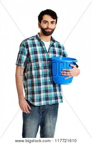 Handsome man holding plastic bucket.