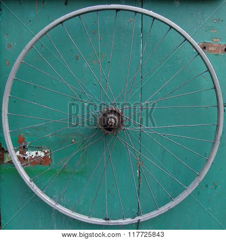 Old Bicycle Wheel On Green Wooden Grungy Background