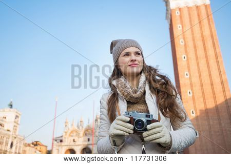 Pensive Woman Holding Camera In Front Of Campanile Di San Marco