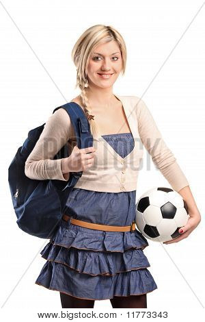Female High School Student Wearing School Bag And Holding A Football
