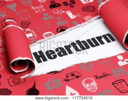 Medicine concept: black text Heartburn under the piece of  torn paper