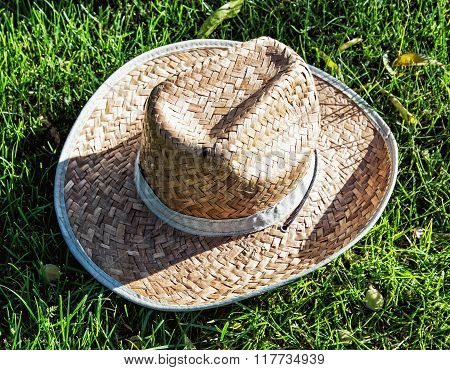 Farmer's Yellow Straw Hat In The Grass