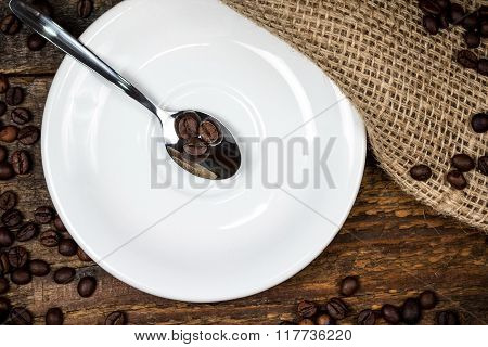 Coffee Beans On Spoon With White Plate And Surrounding Coffeebeans