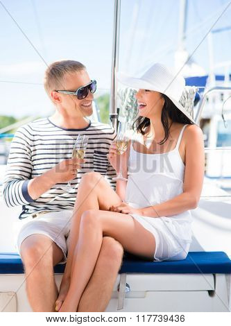 Young and beautiful couple have a party on a luxury sailing boat at summer.