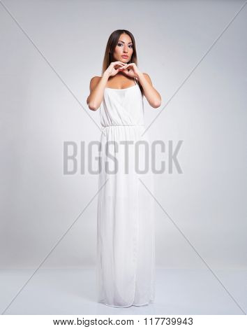 Gorgeous, young lady wearing peplos over grey background.