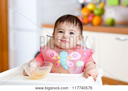 Baby girl eating with spoon and sitting in a high chair for feeding