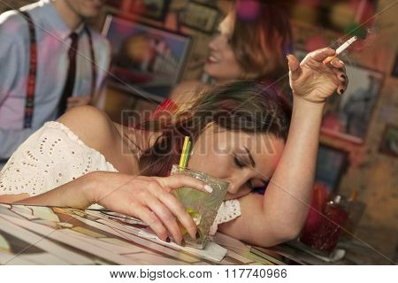 Woman lays her head on the arm as she stands at the bar and smokes a cigarette
