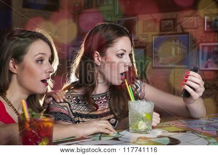 Two women look surprised at the screen of the mobile phone
