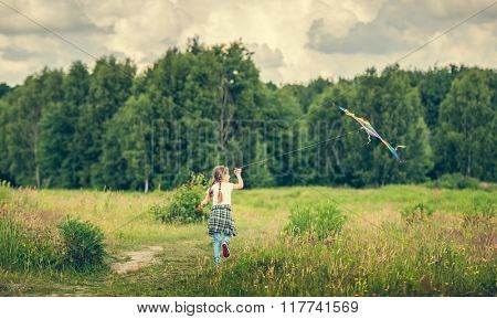 little cute girl flying a striped kite in a meadow on a sunny day. back view