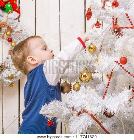 cute little boy standing near christmas tree with presents and decorations