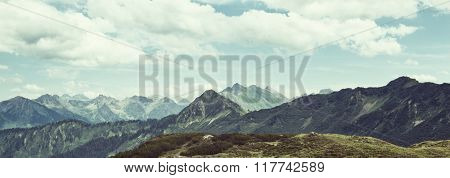 Panoramic scenic landscape of alpine peaks and mountain ranges in the distance under a cloudy blue sky